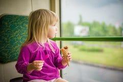 Den förtjusande flickan äter glassridningbussen Arkivfoton