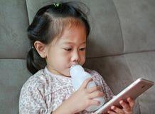 Den f?rtjusande flickan f?r det lilla barnet som spelar den smarta telefonen och dricker, mj?lkar med sugr?r p? den gr?a soffan h royaltyfri fotografi