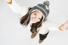 Den förtjusande flickan i vinter beklär att se upp med lyftta armar. Arkivfoton