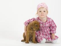 Den förtjusande flickan kramar henne valpen Fotografering för Bildbyråer