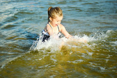 Den förtjusande lilla flickan är plaskande och fantastiskt havsvatten och hagyckel Royaltyfri Bild