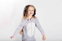 Den förtjusande lilla flickan i hörlurar tycker om med en musik Arkivbild