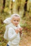 Den förtjusande lilla flickan kramar hennes favorit- mjuka leksak i en sommardag i parkera arkivfoto