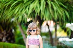 Den förtjusande lilla flickan på den tropiska semesterorten som står vid, gömma i handflatan tre på den soliga sommardagen royaltyfri bild