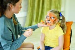 Den förtjusande lilla flickan som får hennes framsida, målade som tiger av konstnären Royaltyfria Foton