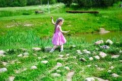 Den förtjusande lilla flickan som går på, vaggar vid ett damm i solig medeltal Arkivbilder