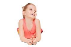 Den förtjusande lilla flickan som har att le för gyckel, är liggande se till sidan som isoleras på vit bakgrund royaltyfria bilder