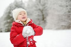 Den förtjusande lilla flickan som har gyckel i härlig vinter, parkerar Gulligt barn som spelar i en snö arkivfoto