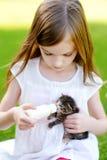 Den förtjusande lilla flickan som matar den lilla kattungen med kattungen, mjölkar från flaskan Fotografering för Bildbyråer