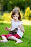 Den förtjusande lilla flickan som matar den lilla kattungen med kattungen, mjölkar från flaskan Royaltyfria Foton