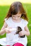 Den förtjusande lilla flickan som matar den lilla kattungen med kattungen, mjölkar från flaskan Royaltyfria Bilder