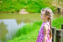 Den förtjusande lilla flickan som spelar vid ett damm i soligt, parkerar på en härlig sommardag Arkivbilder