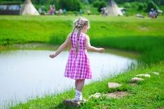 Den förtjusande lilla flickan som spelar vid ett damm i soligt, parkerar på en härlig sommardag Arkivbild