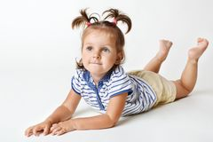 Den förtjusande lilla kvinnliga ungen med den attraktiva blicken, drömlikt uttryck, har två roliga ponnysvansar, lönelyftben uppå arkivbild