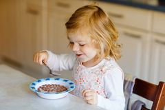 Den förtjusande litet barnflickan som äter sund sädesslag med, mjölkar för frukost som gulligt lyckligt behandla som ett barn bar royaltyfri foto