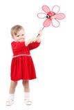 Den förtjusande ljusa ståenden av att spela behandla som ett barn flickan med den röda leksaken Arkivbild