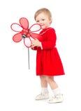 Den förtjusande ljusa ståenden av att spela behandla som ett barn flickan med den röda leksaken Royaltyfria Foton