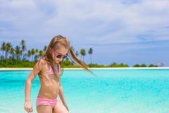 Den förtjusande lyckliga lilla flickan har gyckel på grunt Arkivfoto