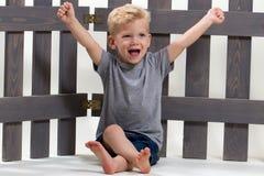 Den förtjusande lyckliga pojken sitter Royaltyfri Foto
