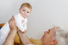 Den förtjusande lyckliga sunda farfadern som rymmer, behandla som ett barn flickabarnbarnet på armar Hög man och gulligt liten fl royaltyfri foto