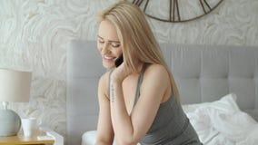 Den förtjusande mitt åldrades den blonda kvinnan som sitter på säng och talar på mobiltelefonen