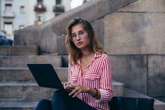 Den förtjusande nätta studenten sitter på trappa med bärbara datorn arkivfoto
