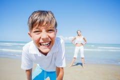 Den förtjusande pojken med hans syster har gyckel på stranden Royaltyfria Bilder