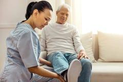 Den förtjusta angenäma sjuksköterskan som ser hennes patienter, lägger benen på ryggen Arkivbild