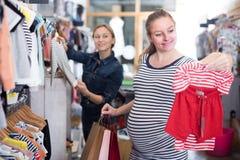 Den förväntansfulla modern i randig tunika väljer kläder för flicka royaltyfri bild