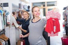 Den förväntansfulla modern i randig tunika väljer kläder för flicka arkivbilder