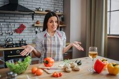 Den förväxlade unga kvinnan sitter på tabellen i kök Hon rymmer händer åt sidan och ser på kamera Exponeringsglas av vin och grön arkivfoton