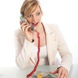 Den förvånada kvinnan på en landline ringer royaltyfri fotografi