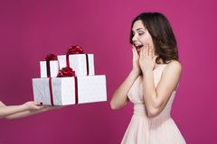 Den förvånade brunetten i en rosa klänning tar många gåvor arkivfoton