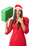 Den förvånade flickan i jultomten en hjälpredahatt rymmer en grön gåva Royaltyfria Foton