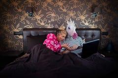 Den förvånade flickan ligger på sängen med den roliga pojkvännen i festlig maskering Fotografering för Bildbyråer