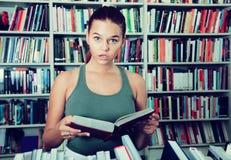 Den förvånade flickan väljer en bok i arkivet arkivfoton