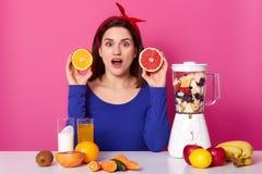 Den förvånade härliga kvinnan rymmer skivan av apelsinen, och grapefrukten, har chockat uttryck, öppnar munnen från häpnad som om royaltyfria foton