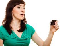 Den förvånade kvinnan läser meddelandet på hennes mobiltelefon Arkivbild