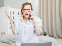 Den förvånade kvinnan, den förvånade kvinnan med den chockade framsidan och öppnar muninnehavtelefonen skri arkivbilder