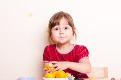 Den förvånade lilla flickan renar mandarinen Royaltyfri Bild