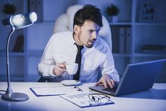 Den förvånade mannen arbetar på bärbara datorn i regeringsställning och dricker ett kaffe Royaltyfri Bild