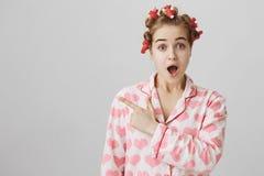 Den förvånade och chockade flickaktigt flickan i papiljotter och pyjamas med hjärta skrivar ut lämnat att indikera med pekfingret royaltyfri foto