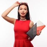 Den förvånade spensliga unga kvinnan i en röd klänning och koppling rymmer på till solglasögon i formen av en hjärta Arkivfoton