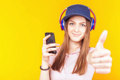 Den förvånade tonårs- flickan använder hörlurar och mobiltelefonen Arkivbild