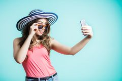 Den förvånade unga kvinnan tar en selfie, den roliga framsidan, grimas Flickan bar en hatt royaltyfri fotografi