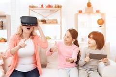 Den förvånade vuxna kvinnan i virtuell verklighetexponeringsglas sitter på soffan bredvid hennes sondotter och sonson, som rymmer royaltyfria bilder