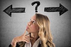 Den förvirrade affärskvinnan måste välja den högra vägen arkivfoton