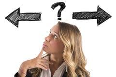 Den förvirrade affärskvinnan måste välja den högra vägen royaltyfria foton