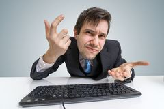 Den förvirrade frustrerade mannen arbetar med datoren Arkivbilder