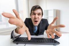 Den förvirrade ilskna affärsmannen arbetar med datoren i regeringsställning royaltyfria bilder